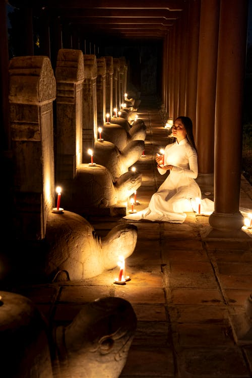Lady in white dress sitting and praying in dark temple near stone sculptures with candles