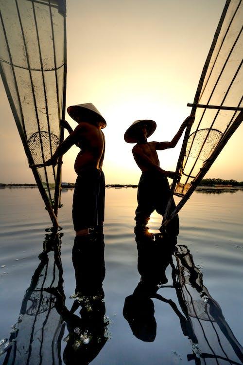 2 Men Standing on Boat