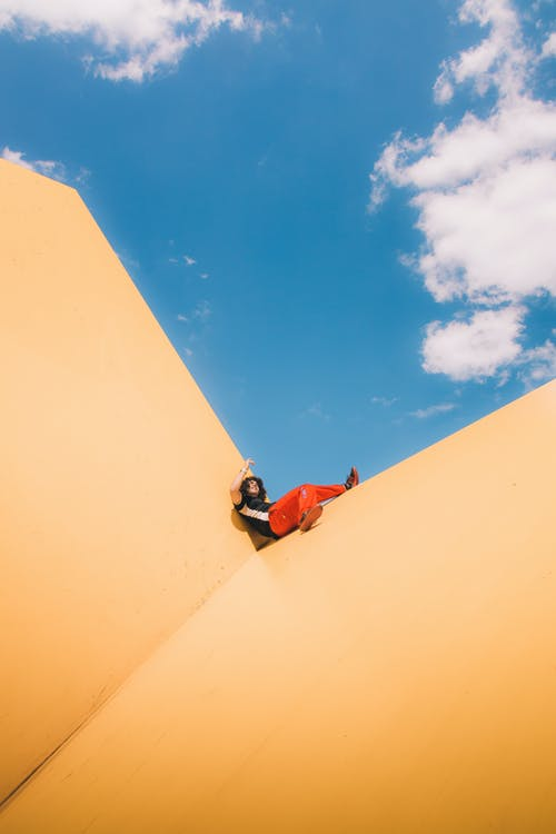 Man in Red Shirt and Blue Denim Jeans Sitting on Brown Sand Under Blue Sky during