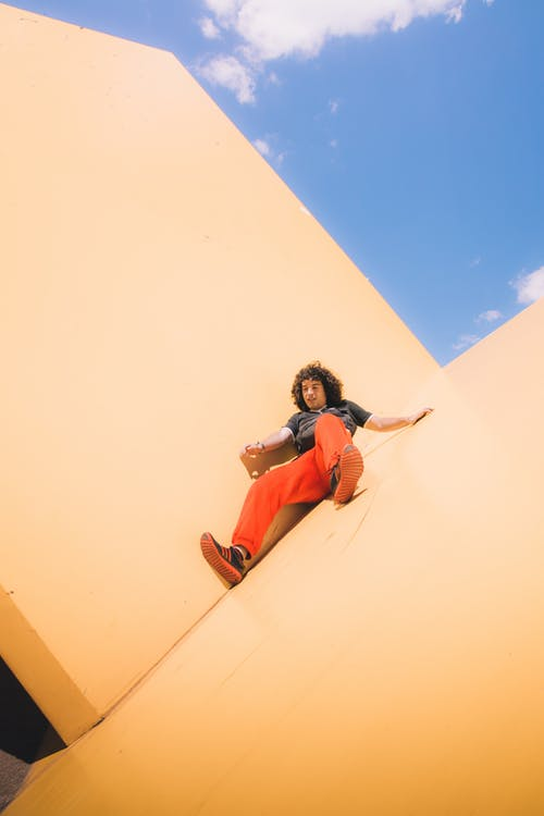 Woman in Blue Shirt and Orange Pants Sitting on Brown Sand