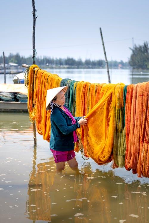 Vietnamese woman choosing fishing nets in coastal village