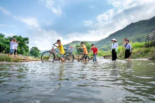 Group of kids and women crossing local river