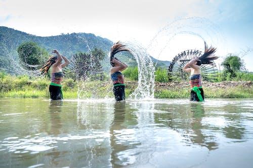 Women shaking hair while washing in river