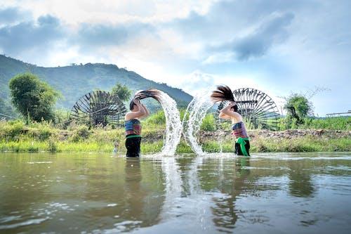 Women washing hair in pond in hilly terrain