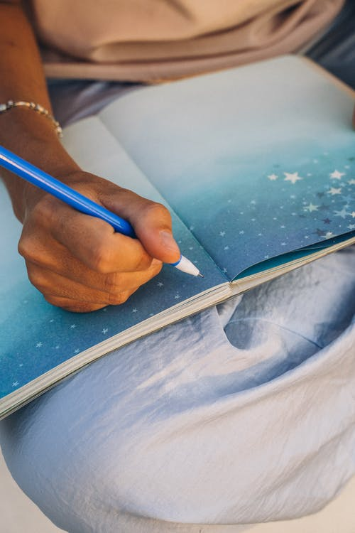 Person Holding Blue Pen on Blue Paper