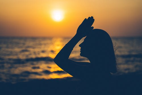 Silhouette of Woman Covering Her Face With Her Hands during Sunset