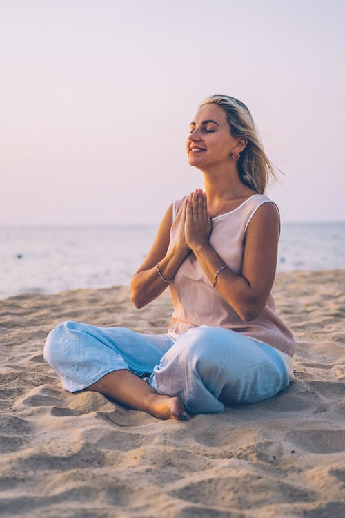 Woman in White Tank Top and Blue Denim Jeans Sitting on Beach Sand