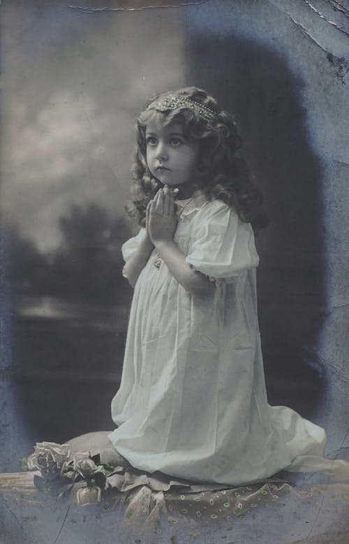 Little Girl in White Dress With Headress Praying