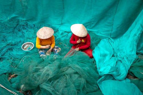 Unrecognizable women in Vietnamese hats repairing fishing nets