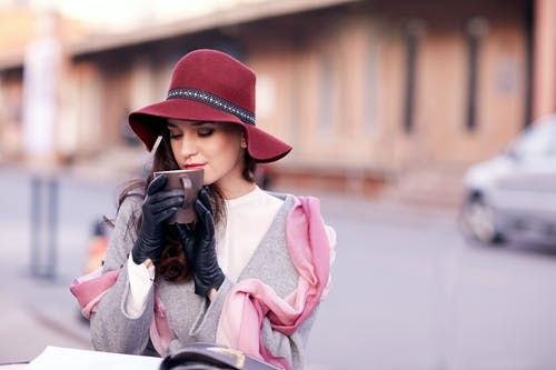 Fashionable young lady with long dark hair in stylish outfit and hat drinking aromatic coffee in street cafe