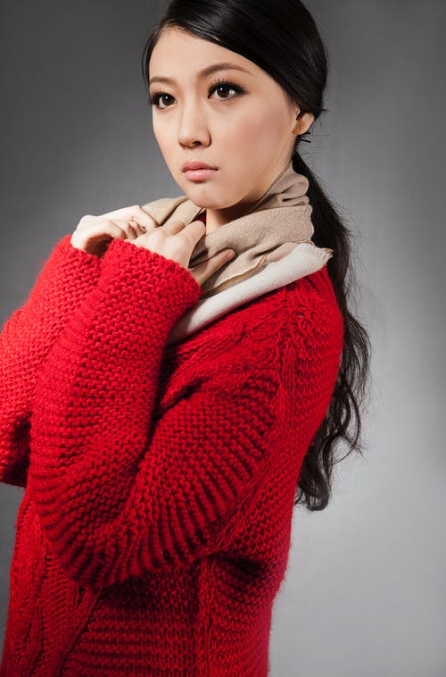 Side view of crop pensive young Asian female model with long dark hair in fashionable knitted cardigan and scarf standing against gray background and looking away