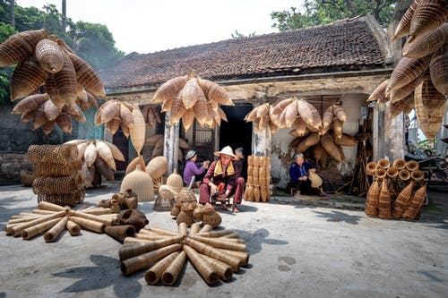 Many traditional Vietnamese timber wicker fish traps near rural residential building and aged ethnic people