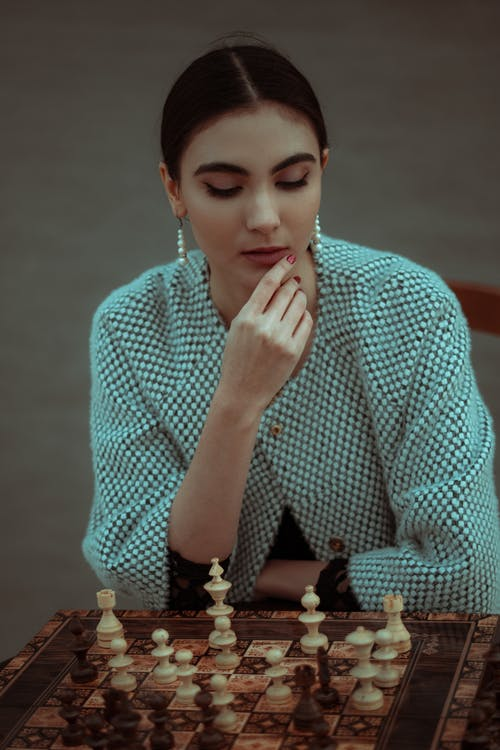 Young contemplative female touching chin in thoughts and playing chess game in studio