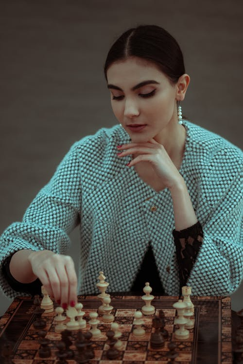 Contemplative woman making move in chess game