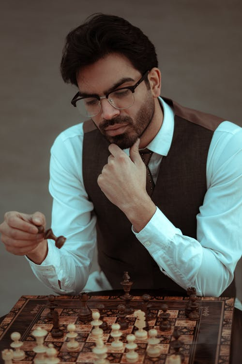 Pensive bearded male in classy wear playing chess and touching chin in contemplation
