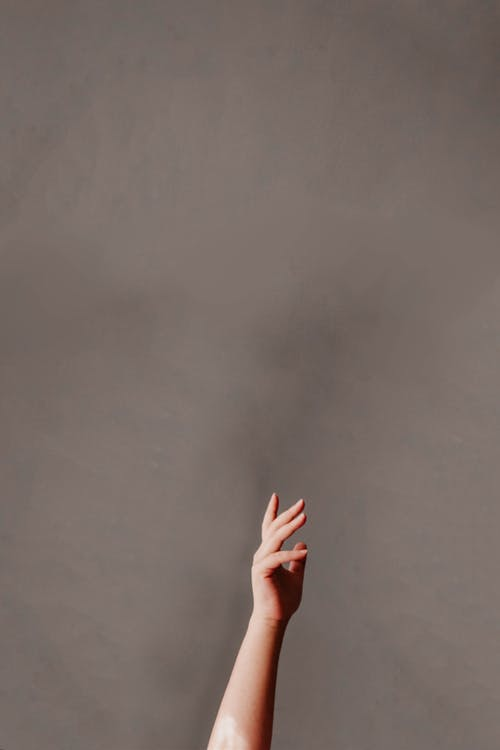 Persons Hand on Gray Wall