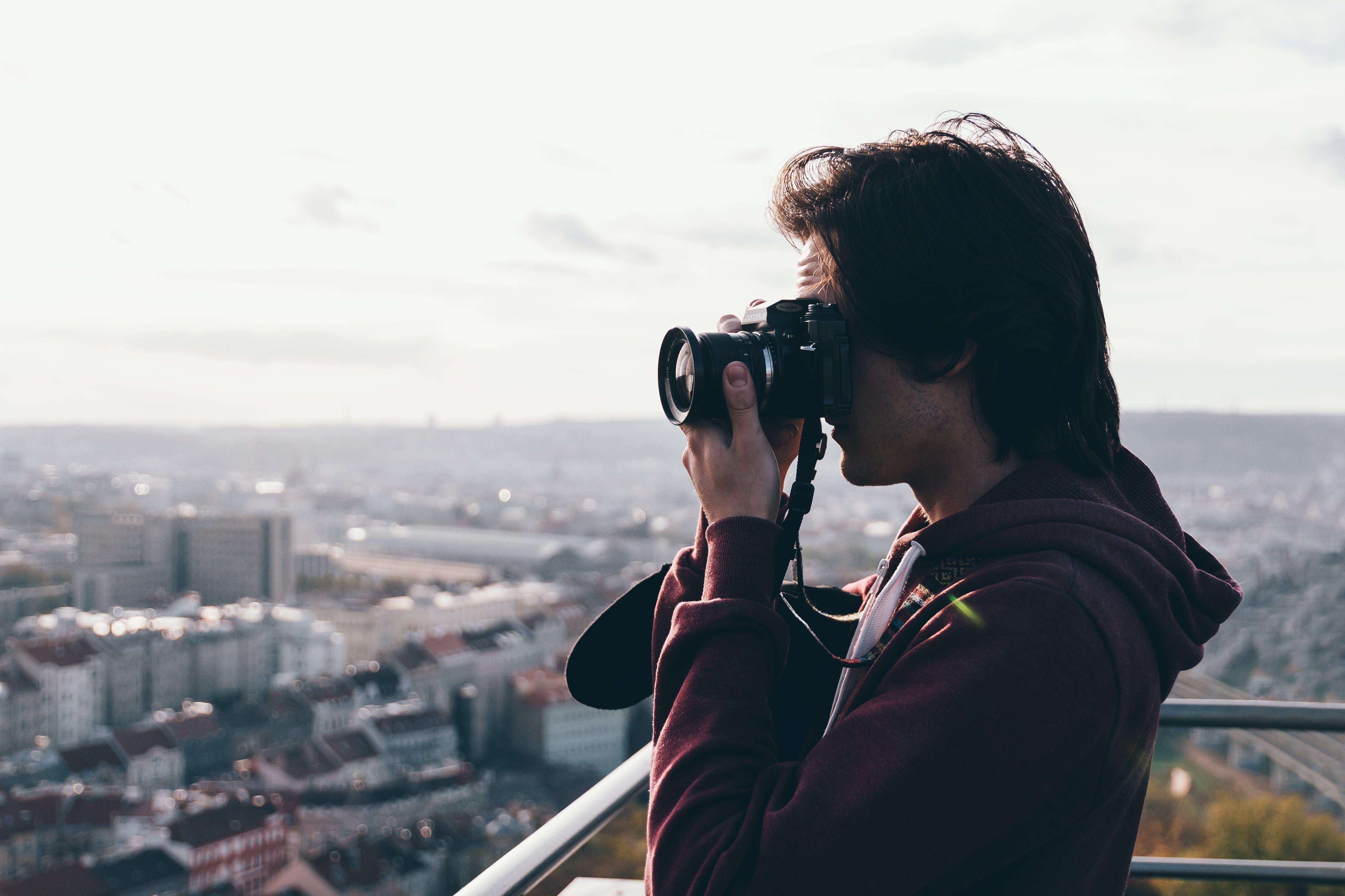 Man in Maroon Jacket Using Camera