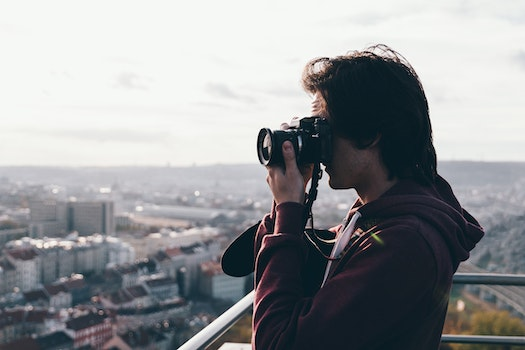 Man in Maroon Jacket Using Camera