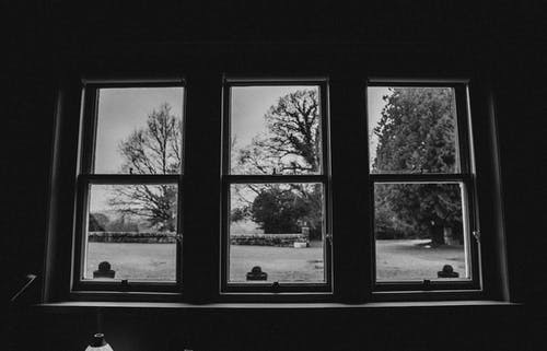 Grayscale Photo of Window With a View of a City