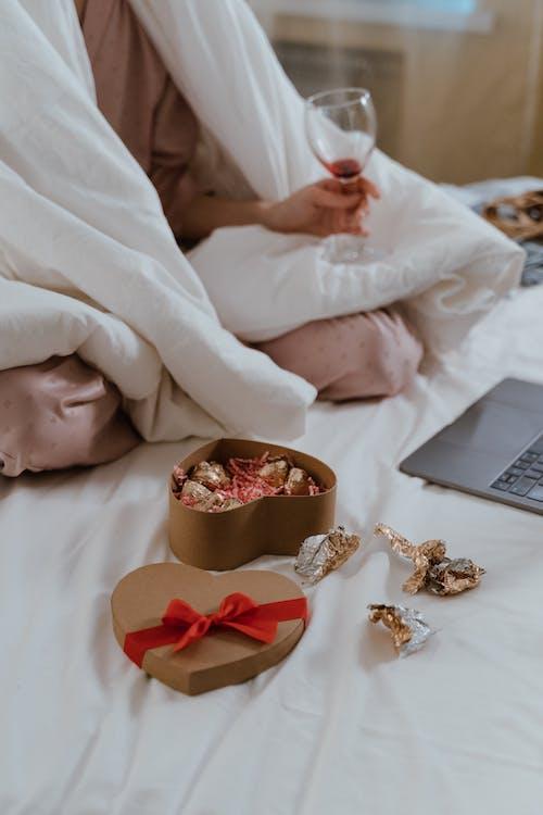 Gratis stockfoto met dekbed, doos chocolaatjes, nachtkleding