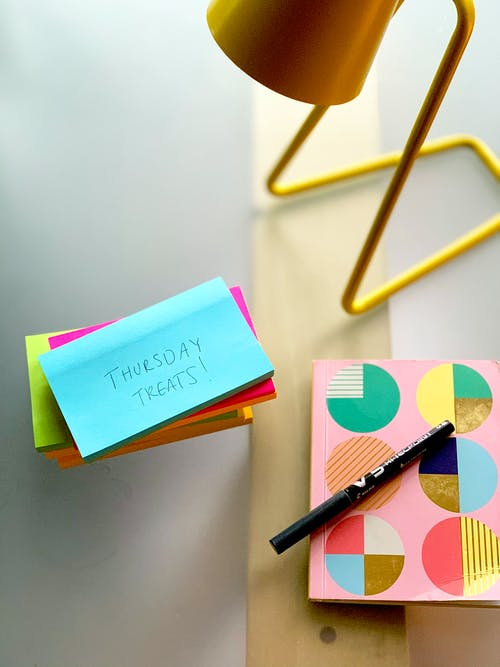 A Close Up Photo of a Lamp, Sticky Notes, Pen, and Notebook
