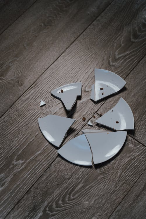 Close-Up Shot of Shards of a Broken Ceramic Plate on a Wooden Surface