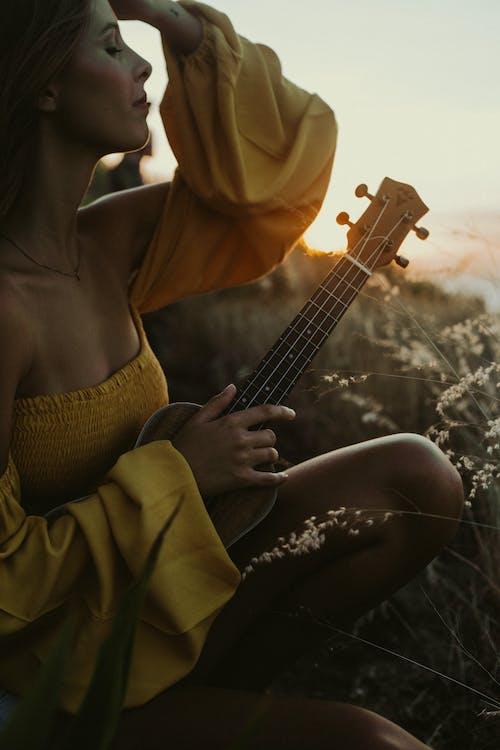 Woman in Yellow Hijab Playing Guitar