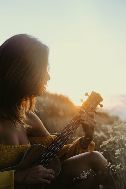 Woman Playing Guitar during Sunset