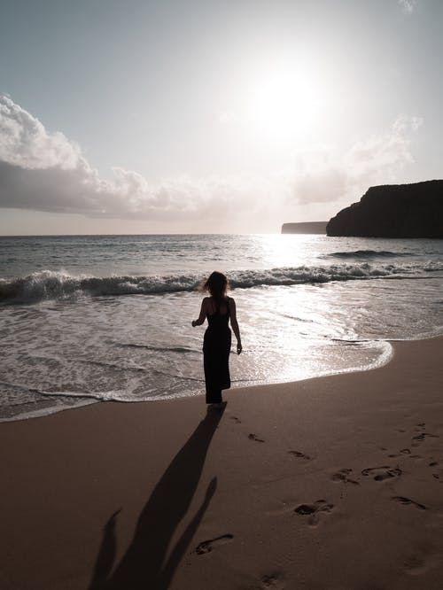Back View of a Woman Walking at the Beach During Daytime
