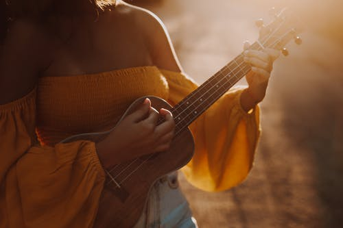 Woman in Brown Knit Sweater Playing Acoustic Guitar