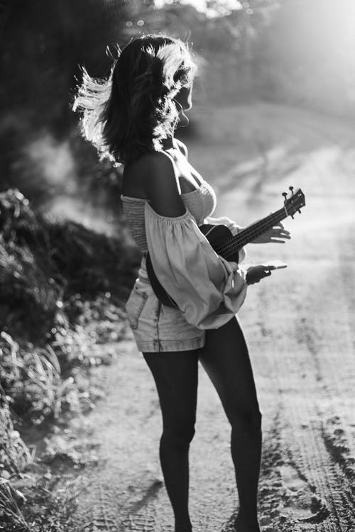 Woman in White Tank Top Playing Violin