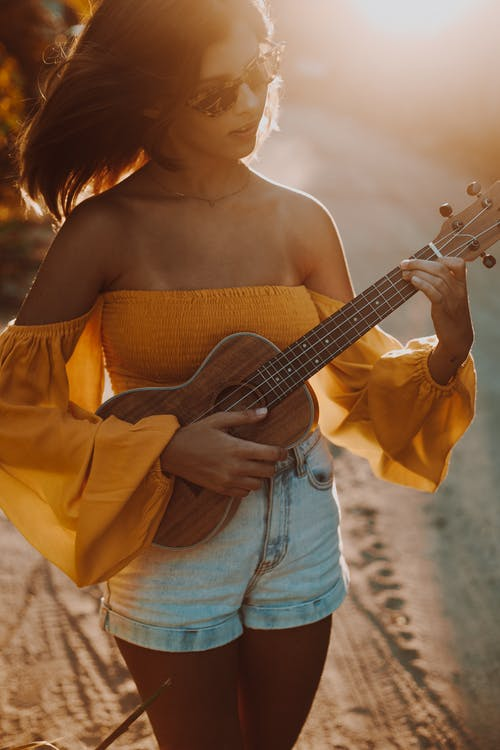 Woman in Yellow Off Shoulder Dress Holding Brown Acoustic Guitar
