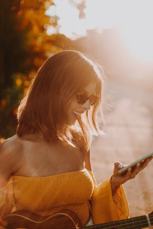 Woman in Yellow Tube Dress Holding Smartphone