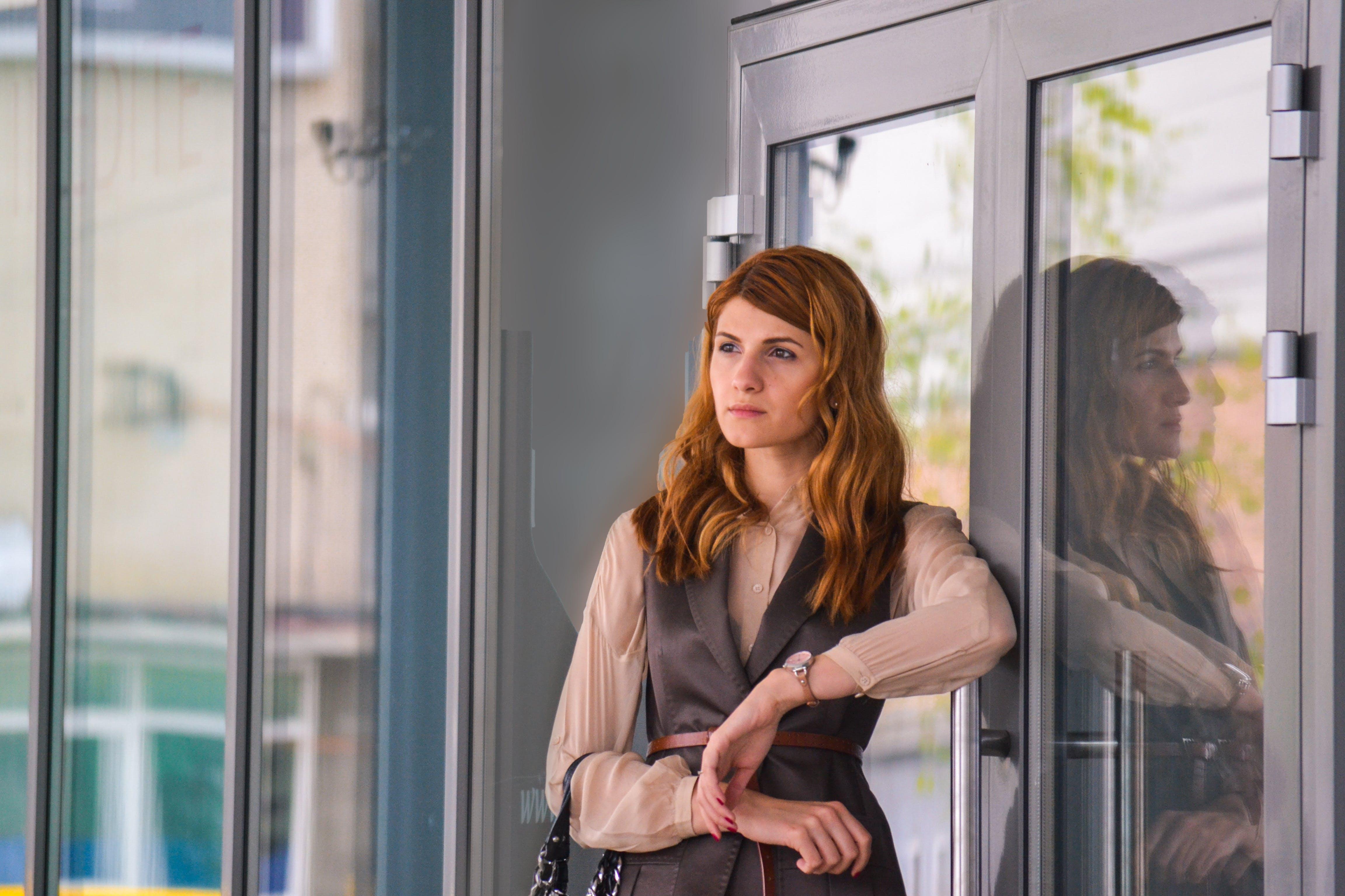 Woman Standing Near Clear Glass Gray Framed Door Panel