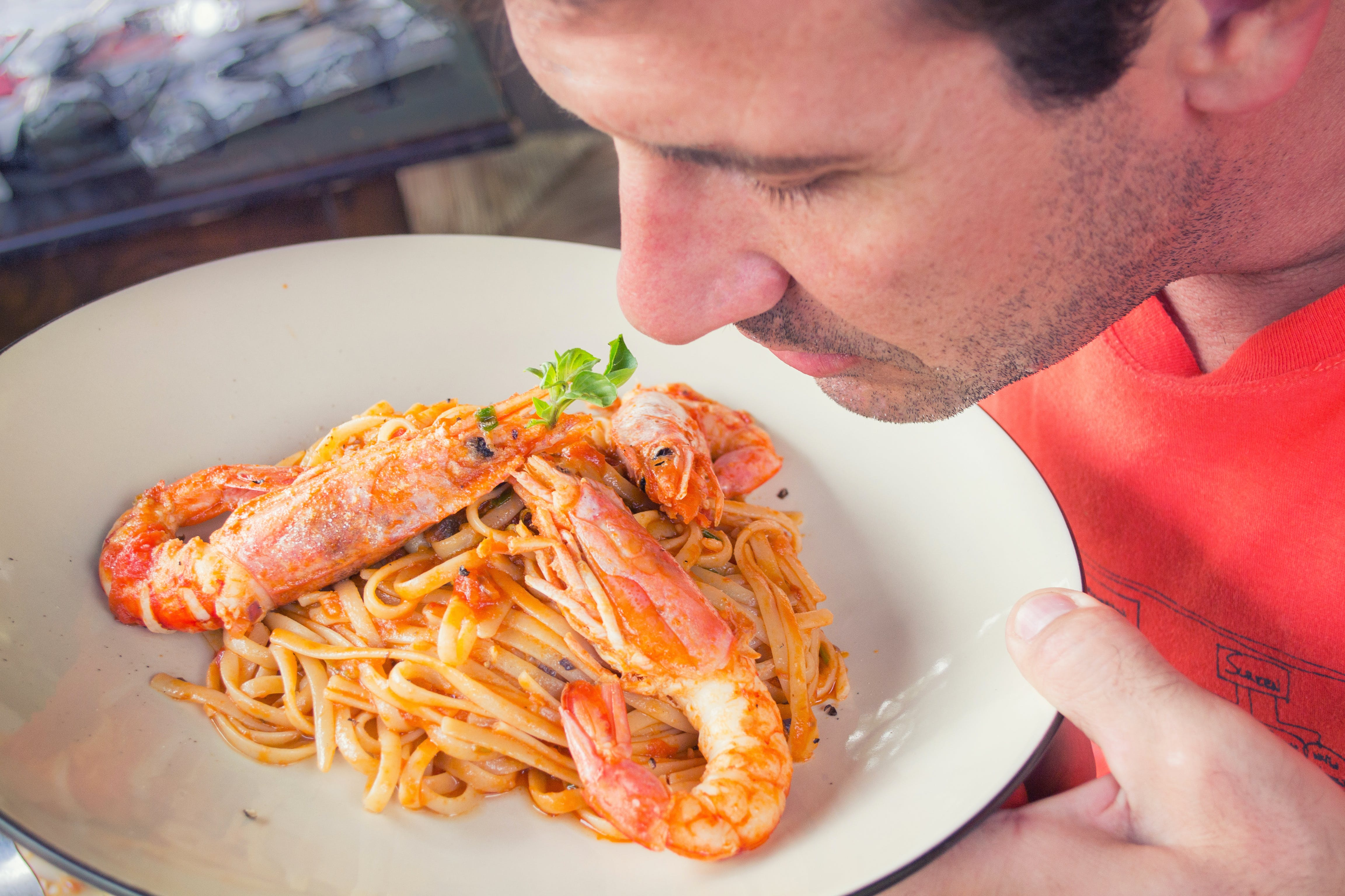 Man Smelling Prawn and Pasta Dish on White Ceramic Plate