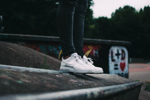 Human Standing on the Ground and Wearing White Nike Sneakers