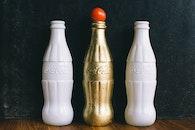 Three White and Brass Coca-cola Bottles