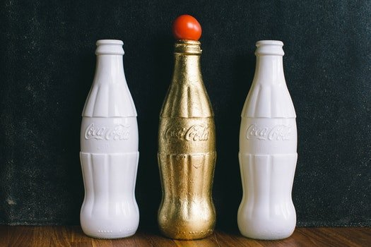 Three White and Brass Coca-cola Bottles