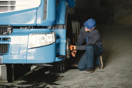Man in Blue Cap Repairing Blue Truck's Wheel