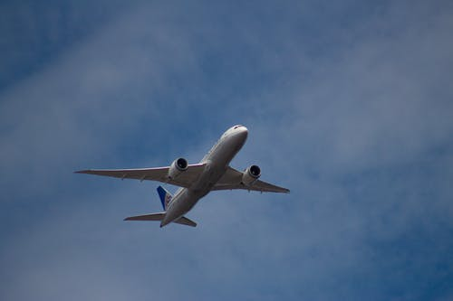 From below of modern majestic large airplane flying across bright blue cloudy sky in sunny weather