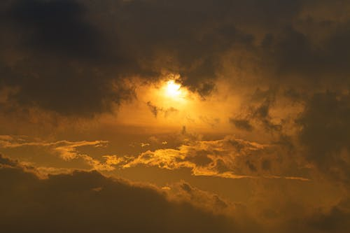 Shiny sky with bright sun among cumulus clouds