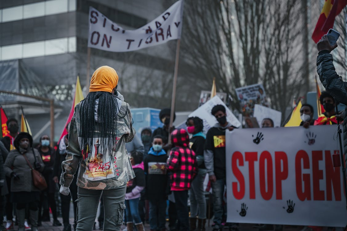 Group of African American people wearing medical masks standing with banners while participating in demonstration against racism on street during pandemic