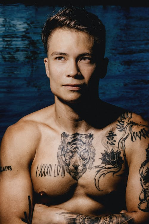 Muscular ethnic young male with tattoos near water