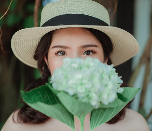 Woman Wearing White Hat Holding Flowers