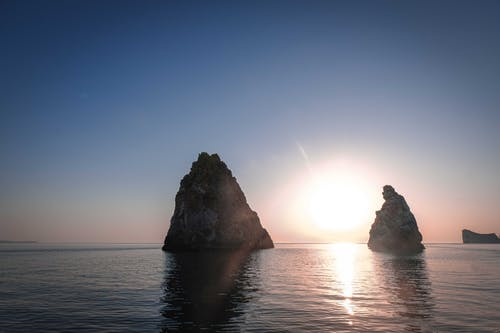 Spectacular scenery of sharp rocky cliffs in rippling water of endless ocean against amazing cloudless sunset sky