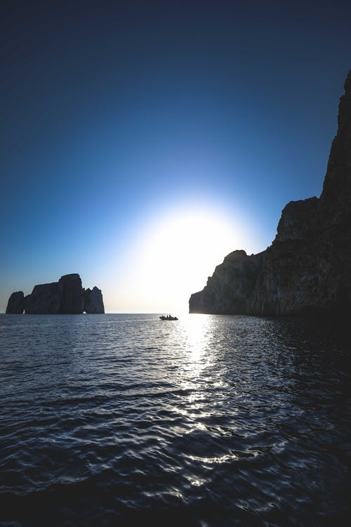 Silhouettes of rocky formations and boat in rippling ocean in sunlight