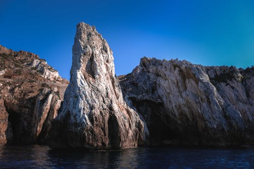 Picturesque rocky cliffs with grotto washing by rippling sea water against bright cloudless blue sky on sunny day