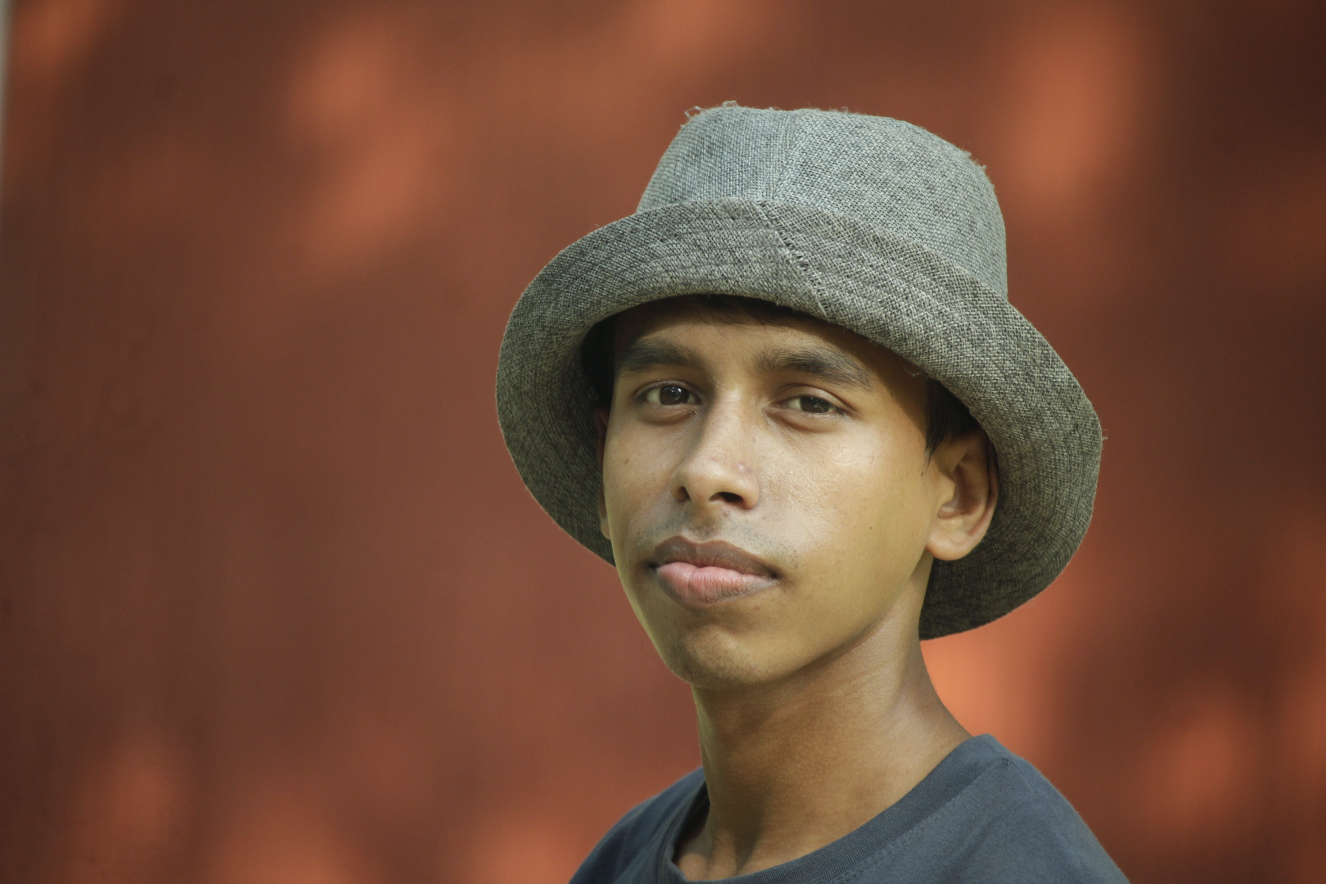 Selective Focus Photography of Man Wearing Gray Fedora Hat and Gray Crew-neck Shirt