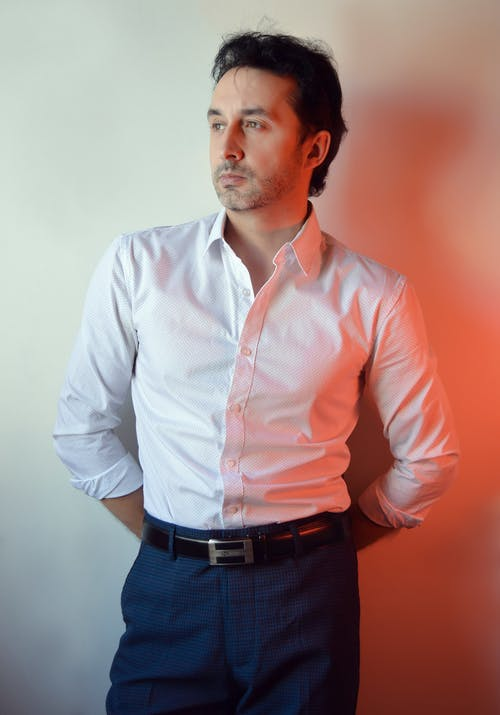 Dreamy adult male entrepreneur with beard in white shirt looking away with hands behind back