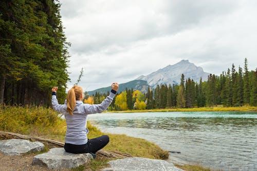 Woman in Grey Hoodie Sweater Sitting on Rock Near Body of Water